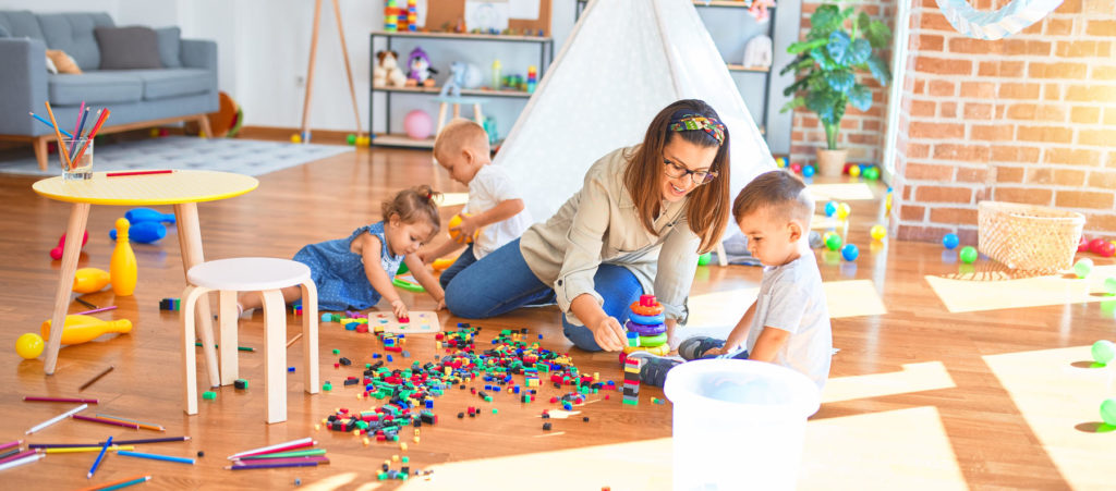 Toddler teacher and group of toddlers playing around lots of toys at kindergarten - Preschool & Daycare Serving Berlin, Northboro & Clinton MA